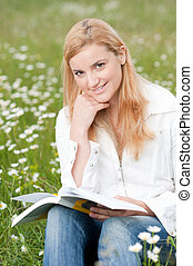 Beautiful young woman reading a book outdoors on a grass field in park