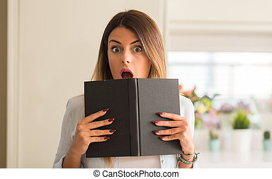 Beautiful young woman reading a book shocked and amazed at home.