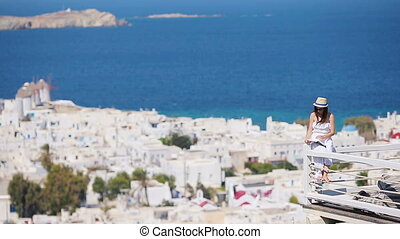 Beautiful young woman reading book in luxury hotel with amazing view on Mykonos, Greece
