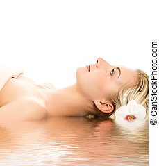 Beautiful young woman ready for spa treatment near the water