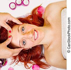 Beautiful young woman receiving facial massage in a spa salon