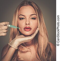 Beautiful young woman red lips with syringe