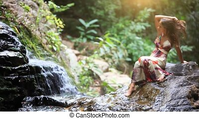 Beautiful young woman relaxing in a wonderful forest near waterfall. Koh Samui. Thailand. Hd. 1920x1080