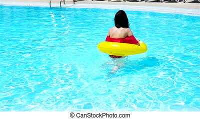 Beautiful young woman relaxing in swimming pool. Happy girl...