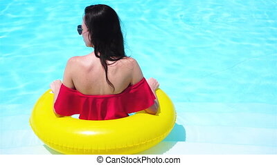 Beautiful young woman relaxing in swimming pool. Back view...