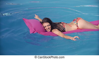 Beautiful young woman relaxing in swimming pool in summer,...