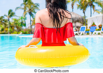 Beautiful young woman relaxing in swimming pool.