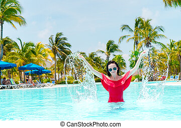 Beautiful young woman relaxing in swimming pool. Happy girl in outdoor pool at luxury hotel