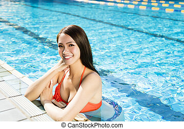 beautiful young woman relaxing in swimming pool