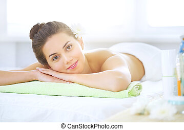 Beautiful young woman relaxing in the spa salon