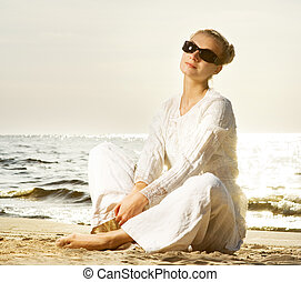 Beautiful young woman relaxing on a beach
