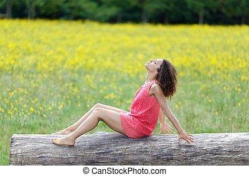 Beautiful young woman relaxing on a log