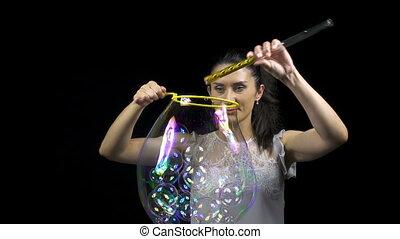Beautiful young woman releasing soap bubbles