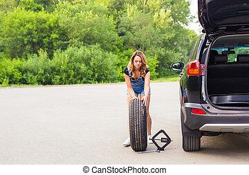 beautiful young woman repairing the car