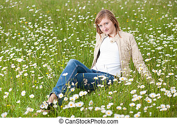 Beautiful young woman resting on a grass field in park