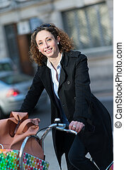 beautiful young woman riding bicycle in town