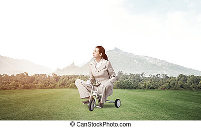 Beautiful young woman riding children's bicycle