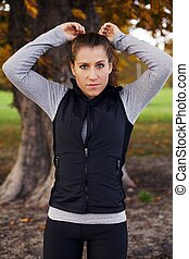 Beautiful young woman runner standing in park