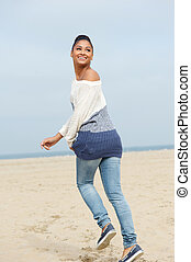 Beautiful young woman running away and smiling