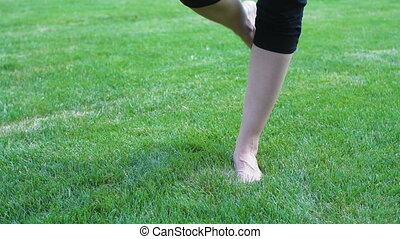 beautiful young woman running barefoot on grass in the summer meadow