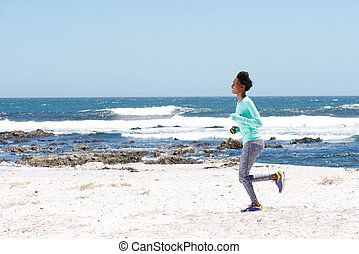 beautiful young woman running by the sea