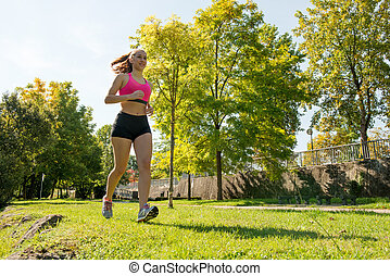 Beautiful young woman running in nature