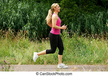 Beautiful young woman running in the park
