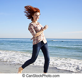 Beautiful young woman running on the beach