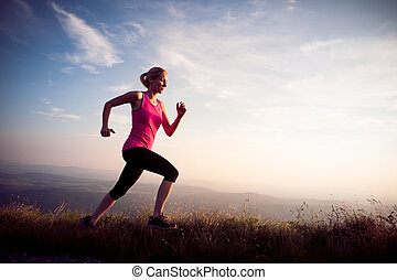 beautiful young woman runns cross country on a mountian path at sunrise