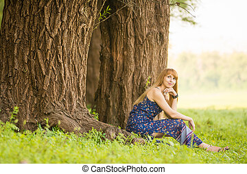 Beautiful young woman sat on the roots of the old large tree and looked up dreamily
