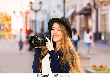Beautiful young woman shooting with camera