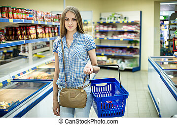 Beautiful young woman shopping for diary products at a grocery store/supermarket
