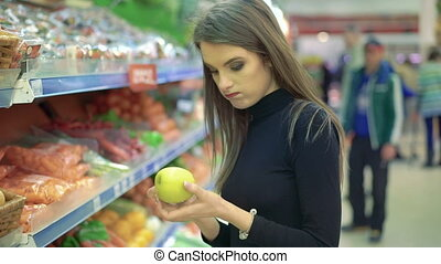 Beautiful young woman shopping for fruits products at a grocery market.