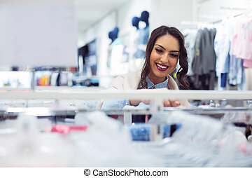 Beautiful young woman shopping in a department store