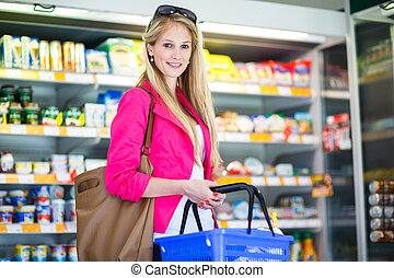 Beautiful young woman shopping in a grocery store/supermarket