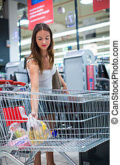 Beautiful young woman shopping in a grocery store