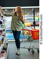 Beautiful young woman shopping in supermarket