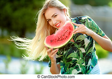 Beautiful young woman showing a slice of watermelon. She is caucasian. Summer and lifestyle concepts.