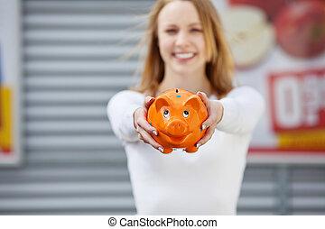 Beautiful young woman showing her piggy bank