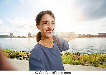 Beautiful young woman showing urban skyline