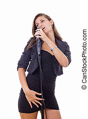 beautiful young woman singing on microphone in black dress
