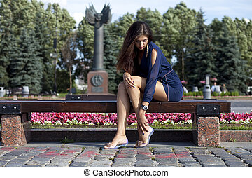 Beautiful young woman sits on a bench