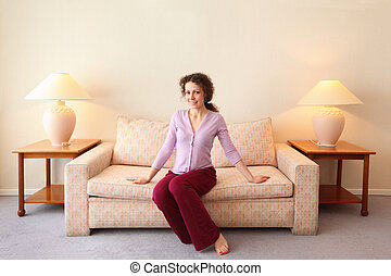 Beautiful young woman sits on couch in simple comfortable room