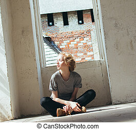 Beautiful young woman sits on the floor of the room.