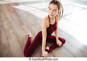 Beautiful young woman sitting and stretching on wooden floor