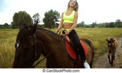 beautiful young woman sitting astride a horse and goes down the street