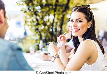 Beautiful young woman sitting at a table outdoors and drinking