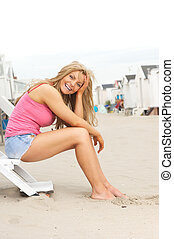 Beautiful young woman sitting at the beach and laughing