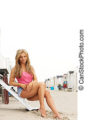 Beautiful young woman sitting at the beach with shorts