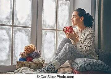 woman sitting by the window - Beautiful young woman sitting...